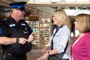 A Police Community Support Officer talking to two members of the public in a shopping centre