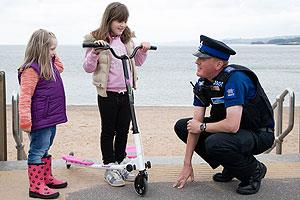 A Police Community Support Officer talking to two children