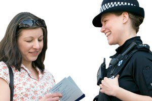 A female police officer handing a booklet of informaiton to a member of the public