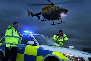 Helicopter and car with flashing blue light with two police officers one on the radio