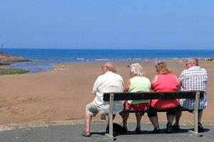 Four people sitting on a bench under a deep blue sky, over looking the sea