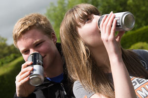 Teenagers drinking alcohol from cans