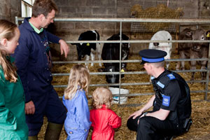 A PCSO talking to some farmers children next to an animal pen