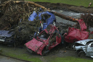 Cars crushed by fallen tree next to fast flowing river