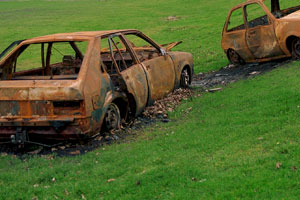 Two burnt out cars in a green feild near a school
