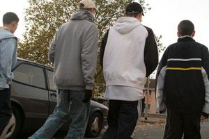 Four teenage boys walking along a residential street wearing jeans caps and hoodies