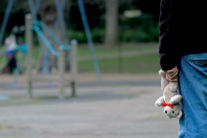 Adult holding teddy in child playground