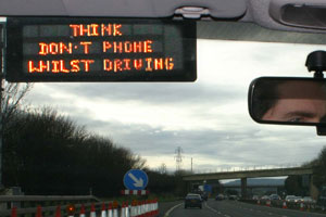View from car front window driving along a motor way with a sign saying Think! don't use mobile whilst driving