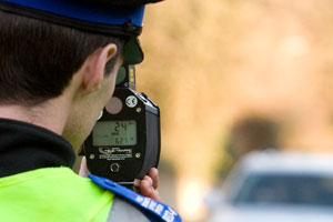 Speed watch: a PCSO with a hand held camera taking speed reading from cars