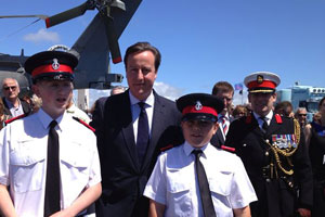Two Police cadets standing in front of a helicopter and the Prime minister