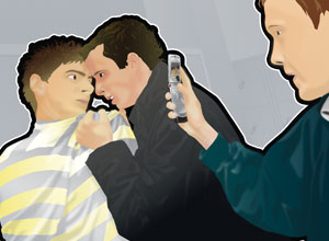 A boy holding another boy while yet a third takes an image using a mobile phone