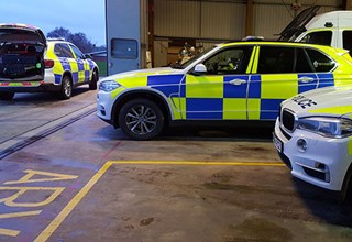 Police cars in helicopter hanger