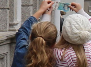 Two girls holding a new 5 pound note upto the light
