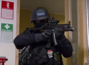 An armed police officer looking for terrorists in a building