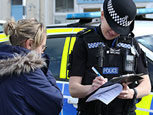 A police woman writting down information a woman is telling her