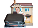 A man opening a suit case in front of a house