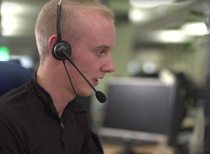 Call handler with headset on talking to a member of the public