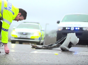 Police officer checking the a road after a collision