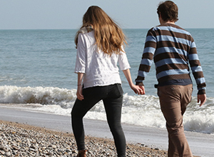 Young couple walking on a pebbly beach hand in hand