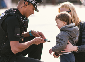 PC crouched down talking to a young child