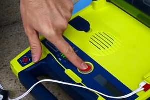 A finger pushing the heart button on a defibrilllator